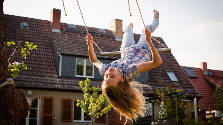 rear view of Girl on a swing in the back yard in front of a small house