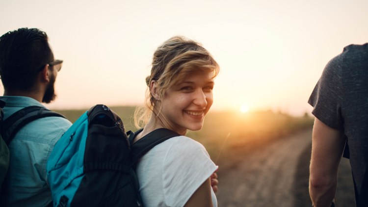 Group of young people hiking together. Closeup of an young smiling woman looking at camera over shoulder. They are walking to sunset.